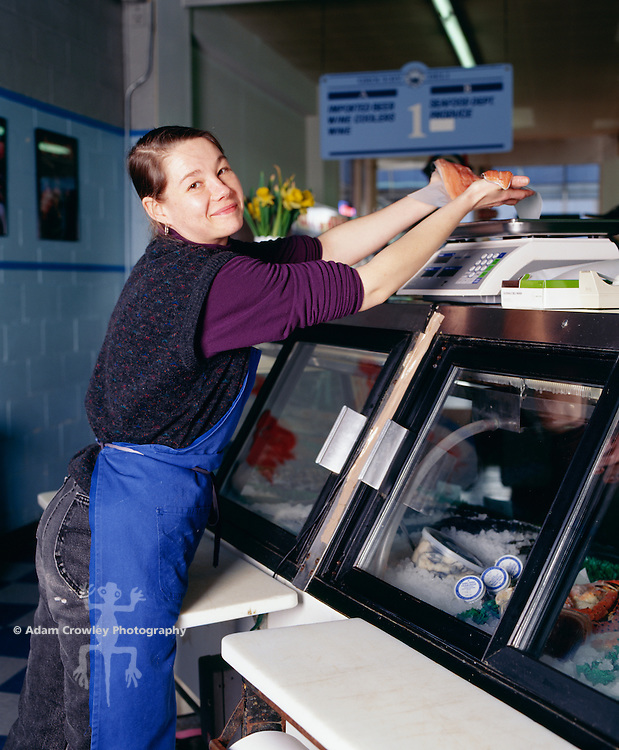 Female worker weighing fish at supermarket, portrait