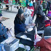 The second day of the Strike WEF march on Davos, 20th of January 2020, Switzerland. Lunch break. Vollunteers doingthe dishes after lunch. Food for 500 people, including sweet donuts and hot drinks was cooked out door by a cooking collective, all vegan and tasty. The march started in Schiers and walked the 24 kilomers to Klosters.  The aim is to finish in Davos with a public meeting in the town on the day the WEF begins. The march is a three day protest against the World Economic Forum meeting in Davos. The activists want climate justice and think that The WEF is for the world's richest and political elite only.