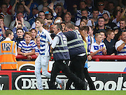Pitch invader being escorted from the ground during the Sky Bet Championship match between Brentford and Reading at Griffin Park, London, England on 29 August 2015. Photo by Matthew Redman.