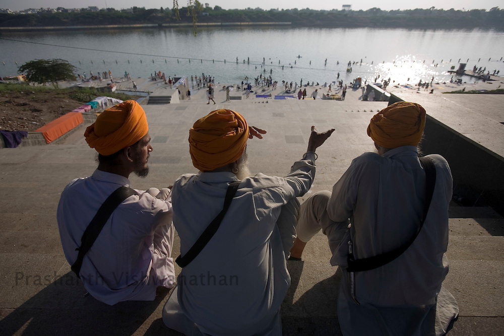 Sikh men watch as others take a holy dip in the Godhavari river during the Khalsa festival celebration in Nanded, 650 kms south of Mumbai on October 30, 2008. Sikhs all over the world are celebrating the 300th year of the consecration of the Sikh holy book, the Guru Granth Sahib. Photographer:Prashanth Vishwanathan