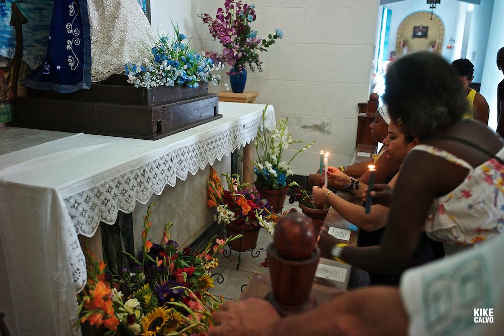 Cuban devotees bringing candles and praying to the Virgin de Regla or Yemaya, Goddess of the Sea