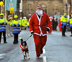 Scott Kelly and his dog Chewy from Bellshill warm up before more than 8000 runners, all dressed as Santa, took part in the annual charity fun run thru the centre of Glasgow, to raise money for charity.<br /> <br /> © Dave Johnston/ EEm
