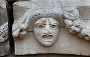 Mask and garland frieze from the Portico of Tiberius on the Southern portico of the Agora, 1st century AD, Aphrodisias, Aydin, Turkey. The Sculpture School at Aphrodisias was an important producer of carved marble sarcophagi and friezes from the 1st century BC until the 6th century AD. The Portico of Tiberius was built under the reign of Tiberius and has many examples of mask and garland friezes, consisting of the heads of gods, goddesses, theatrical characters, mythological figures or masks, each with a distinct facial expression, between hanging garlands of leaves, fruit and flowers. This example is possibly a theatrical mask, or could represent madness. Aphrodisias was a small ancient Greek city in Caria near the modern-day town of Geyre. It was named after Aphrodite, the Greek goddess of love, who had here her unique cult image, the Aphrodite of Aphrodisias. The city suffered major earthquakes in the 4th and 7th centuries which destroyed most of the ancient structures. Picture by Manuel Cohen