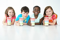 Boys and three girls (5-6) sitting at table holding colourful glasses smiling portrait