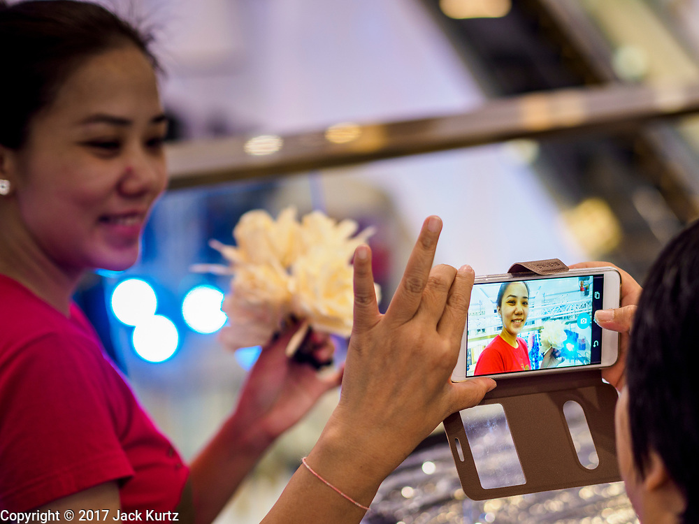 "24 MAY 2017 - BANGKOK, THAILAND: A woman is photographed with her smart phone at the Emporium, an upscale shopping mall in Bangkok. She was making wooden roses to be used during the cremation of Bhumibol Adulyadej, the Late King of Thailand. In Thai culture it is customary to place wooden flowers in front of a deceased person's coffin or urn as a last tribute before cremation. The Royal Cremation Organisation Committee, which is overseeing plans for the cremation of Bhumibol Adulyadej, the Late King of Thailand, asked the Bangkok Metropolitan Administration (BMA) to provide three million wooden flowers for the late King's cremation. The BMA, in turn, has asked malls and civic organizations to provide flowers. The Mall Group, which owns Emporium, has pledged to provide up to one million wooden ""Wiangping"" roses, which in Thai culture symbolize unconditional love. The late King will be cremated October 26, 2017.     PHOTO BY JACK KURTZ"