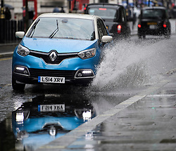 © Licensed to London News Pictures. 26/07/2019. London, UK. A car ploughs through surface water in Westminster, central London as the capital is deluged with rain, following a week that saw the UK experience record temperatures for July. Photo credit: Ben Cawthra/LNP