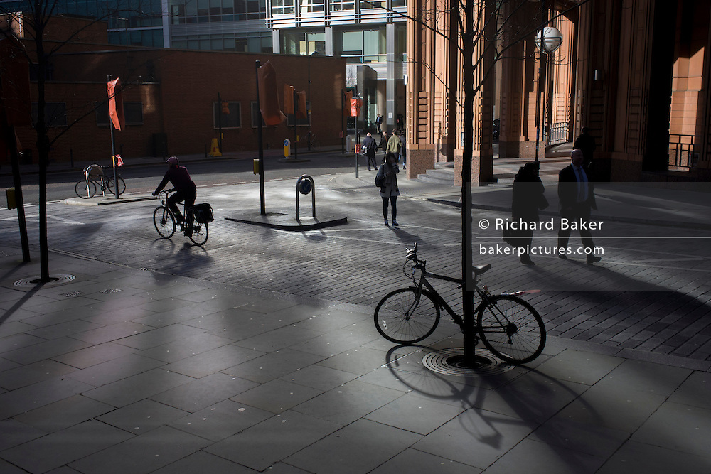 A theme of locked and pedalled bikes on reflected lit street corner in the City of London.