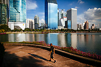 An older Thai man walks through Benjakiti Park near Sukhumvit in downtown Bangkok, Thailand.