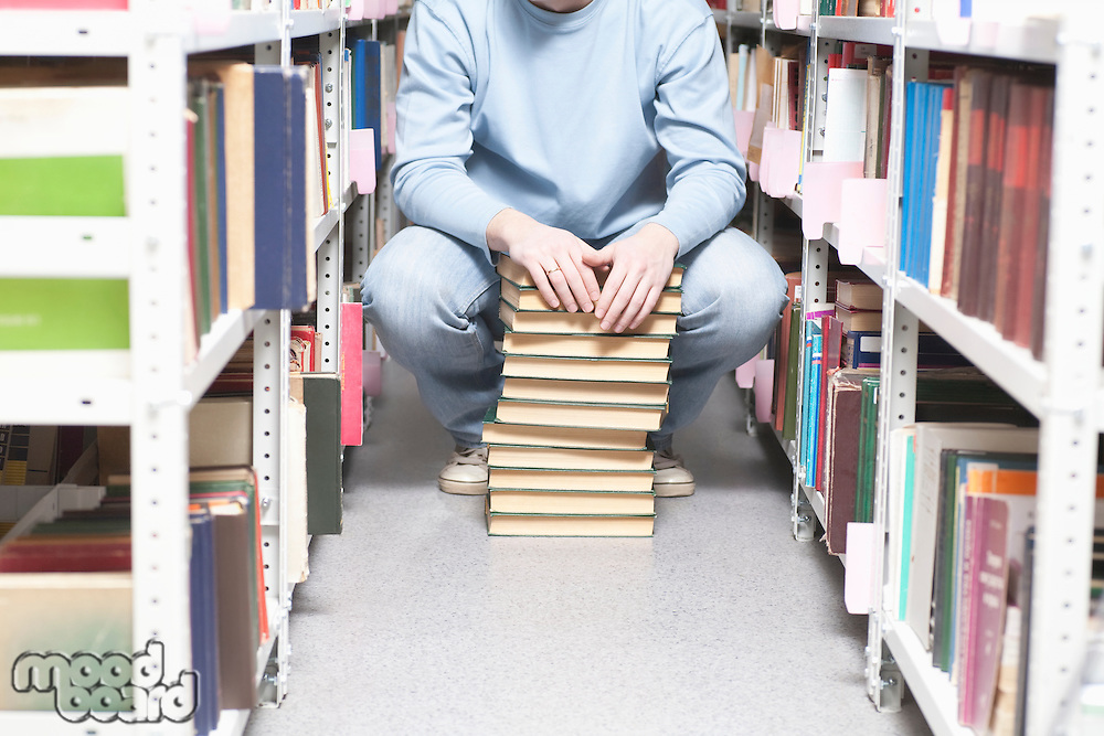 Young man crouches with pile of books in library