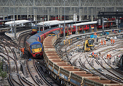 © Licensed to London News Pictures. 15/08/2017. London, UK. A derailed train (L) rests on wagons of a freight train at Waterloo station in London after a low speed collision. Re-building work on the platforms continues (R). People have been advised to avoid using Waterloo station, which is undergoing major development works, for the remainder of the day.  Photo credit: Peter Macdiarmid/LNP