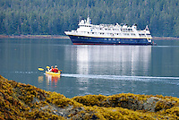 A double kayak in front of a small adventure ship near Pond Island in Southeast, Alaska.