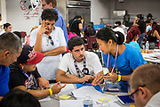 "25 AUGUST 2012 - PHOENIX, AZ:  Volunteers and immigration lawyers who volunteered their time help immigrants complete the paperwork necessary to apply for deferred action status at a workshop in Phoenix. Hundreds of people lined up at Central High School in Phoenix to complete their paperwork to apply for ""Deferred Action"" status under the Deferred Action for Childhood Arrivals (DACA) program announced by President Obama in June. Volunteers and lawyers specialized in immigration law helped the immigrants complete the required paperwork. Under the program, the children of undocumented immigrants brought to the US before they turned 16 years old would not be subject to deportation if they meet a predetermined set of conditions.    PHOTO BY JACK KURTZ"