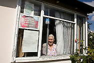 Pamela Clifton behing her living room window in her prefab at the Excalibur estate in Catford, South London. Pamela has been living in her prefab for 40 years and is fighting to save it as the Lewisham Council want to pull the prefabs down.
