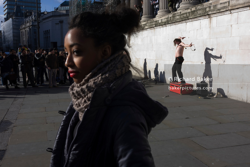 Young woman turns her back on an escapologist busker act at National Portrait Gallery in London's Trafalgar Square.