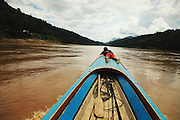 Thailand, Salween river  On the left, Thailand, on the right, Myanmar  in the center, Pochi, a young Karean lie in the front of the long-tail boat, he guide the boat in middle of the floating wood and the numerous Whirlpool.  FR   A gauche, la Thailande, a droite, le Myanmar  Au centre Pochi, un jeune Karen est alongé a laant de la logue barque pour guider a travers les bois flottants et au milieu des nombreux tourbillons.