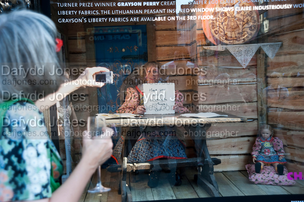 GRAYSON PERRY SKETCHING IN THE LIBERTY'S FRONT WINDOW. Prints Charming Exhibition. Liberty's. London. 11 August 2009