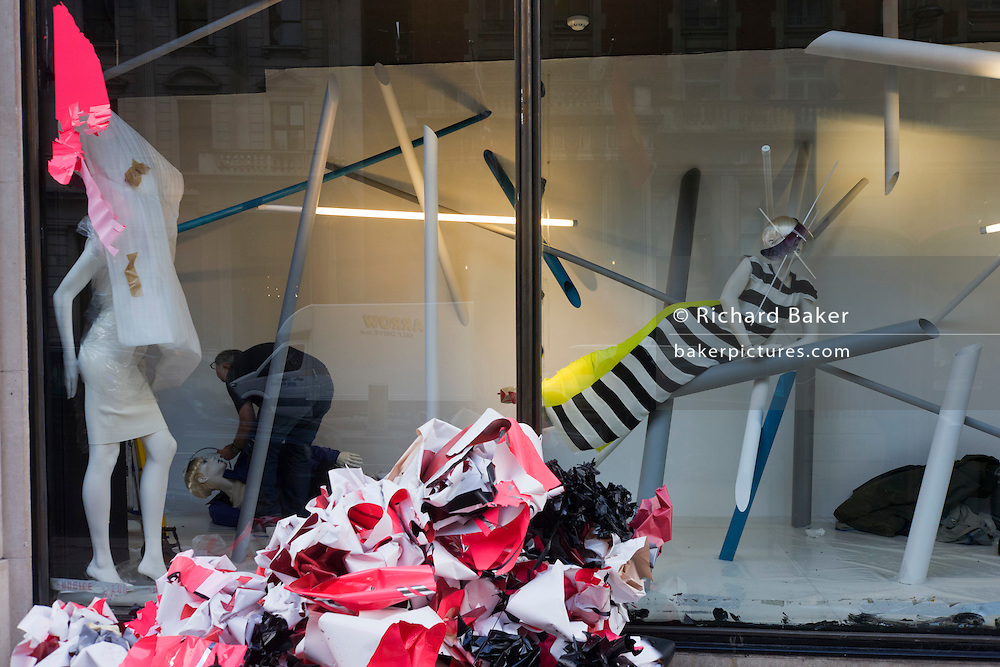A retail window dresser prepares the small features in a new display at the London brance of department store Harvey Nichols.