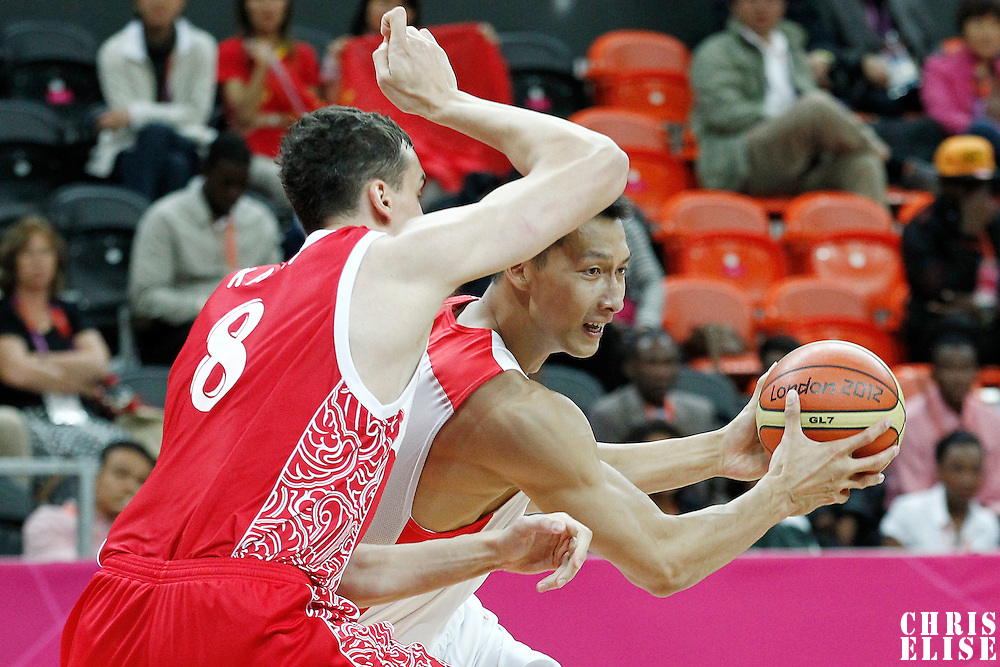 31 July 2012: China Jianlin Yi looks to pass the ball past Russia Sasha Kaun during the 73-54 Russia victory over China, during the men's basketball preliminary, at the Basketball Arena, in London, Great Britain.