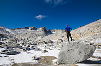 A man standing on a boulder observing the landscape, Enchantment Lakes Wilderness Area, Washington Cascades, USA.