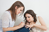 Young woman applying nail paint to friend's fingernails