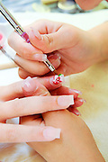 The decoration of false nails with a brush in a manicure salon