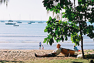 Man resting against boat on the beach at Horseshoe Bay, Magnetic Island, Queensland, Australia.