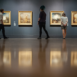 London, UK - 8 September 2014: gallery assistants looks up at paintings from the 1840s<br />  by J.M.W. Turner, during the press preview of The EY Exhibition: Late Turner &ndash; Painting Set Free exhibition at Tate Britain