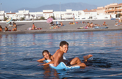 Young children playing on lilo in sea at Salobrena; Andalucia; with the beach and town in background,