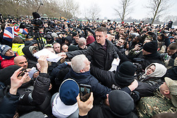 "© Licensed to London News Pictures . 18/03/2018 . London , UK . TOMMY ROBINSON (centre) hands out copies of the speech to the crowd . 1000s including supports of alt-right groups such as Generation Identity and the Football Lads Alliance , at Speakers' Corner in Hyde Park where Tommy Robinson reads a speech by Generation Identity campaigner Martin Sellner . Along with Brittany Pettibone , Sellner was due to deliver the speech last week but the pair were arrested and detained by police when they arrived in the UK , forcing them to cancel an appearance at a UKIP "" Young Independence "" youth event , which in turn was reportedly cancelled amid security concerns . Photo credit: Joel Goodman/LNP"