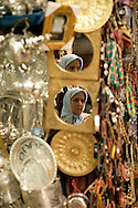 Local woman reflected in a mirror of a souvenir shop. Fez Medina is full of shops, both touristical and traditional ones.