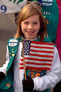 Girl scout age 10 holding the American flag at the Anoka Halloween Festival.  Anoka Minnesota USA