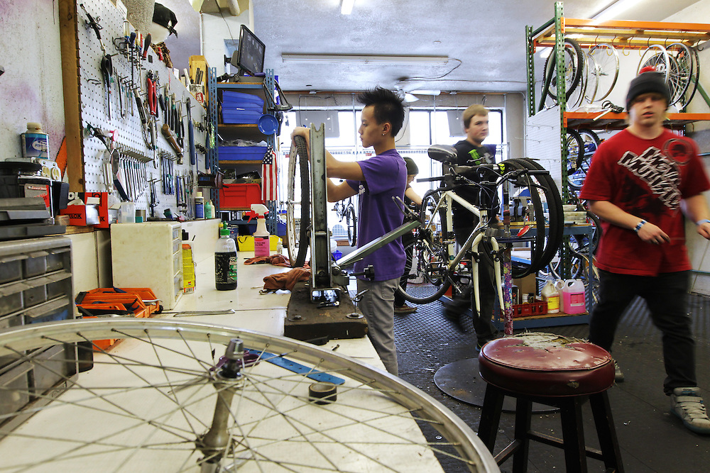 Youth Express apprentice Koua Yang, 15, left, fixes a wheel from a donated bicycle at Express Bike Shop in St. Paul, Minnesota.  By refurbishing and selling bicycles, youth apprentices learn mechanical, business, and entrepreneurial skills. All proceeds from bike sales go towards funding the program.