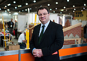 Dr. Stephen Farry Employment and Learning Minister for Northern Ireland visits the ExCel Centre and poses for a portrait in front of the bricklaying stand in London on October 8th 2011.