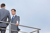 Low angle view of young businessman looking at coworker against clear sky