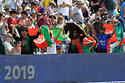 Afghanistan fans running with their flags over their heads during the ICC Cricket World Cup 2019 match between Afghanistan and Australia at the Bristol County Ground, Bristol, United Kingdom on 1 June 2019.