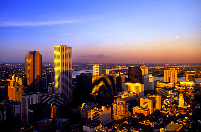 Sunset view of the downtown office buildings of New Orleans.  The Mississippi River can be seen in the background.