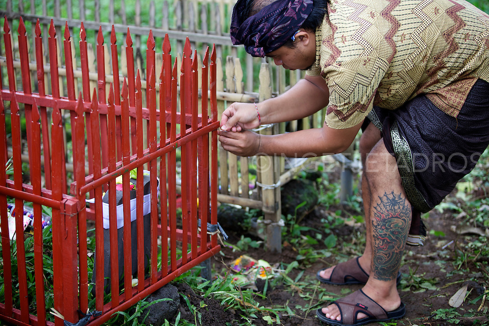 A man is repairing a fence around a grave at a burial site.<br />