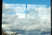 window reflecting indoors against a blue sky with clouds