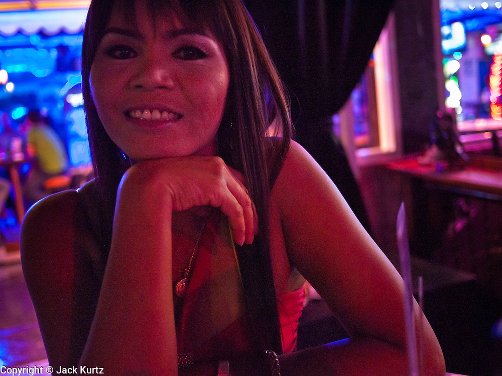 """12 JULY 2011 - BANGKOK, THAILAND:  A worker in the """"Corner Bar"""" on Soi Cowboy in a """"red light"""" district in Bangkok. Prostitution in Thailand is illegal, although in practice it is tolerated and partly regulated. Prostitution is practiced openly throughout the country. The number of prostitutes is difficult to determine, estimates vary widely. Since the Vietnam War, Thailand has gained international notoriety among travelers from many countries as a sex tourism destination. One estimate published in 2003 placed the trade at US$ 4.3 billion per year or about three percent of the Thai economy. It has been suggested that at least 10% of tourist dollars may be spent on the sex trade. According to a 2001 report by the World Health Organisation: """"There are between 150,000 and 200,000 sex workers (in Thailand).""""  PHOTO BY JACK KURTZ"""
