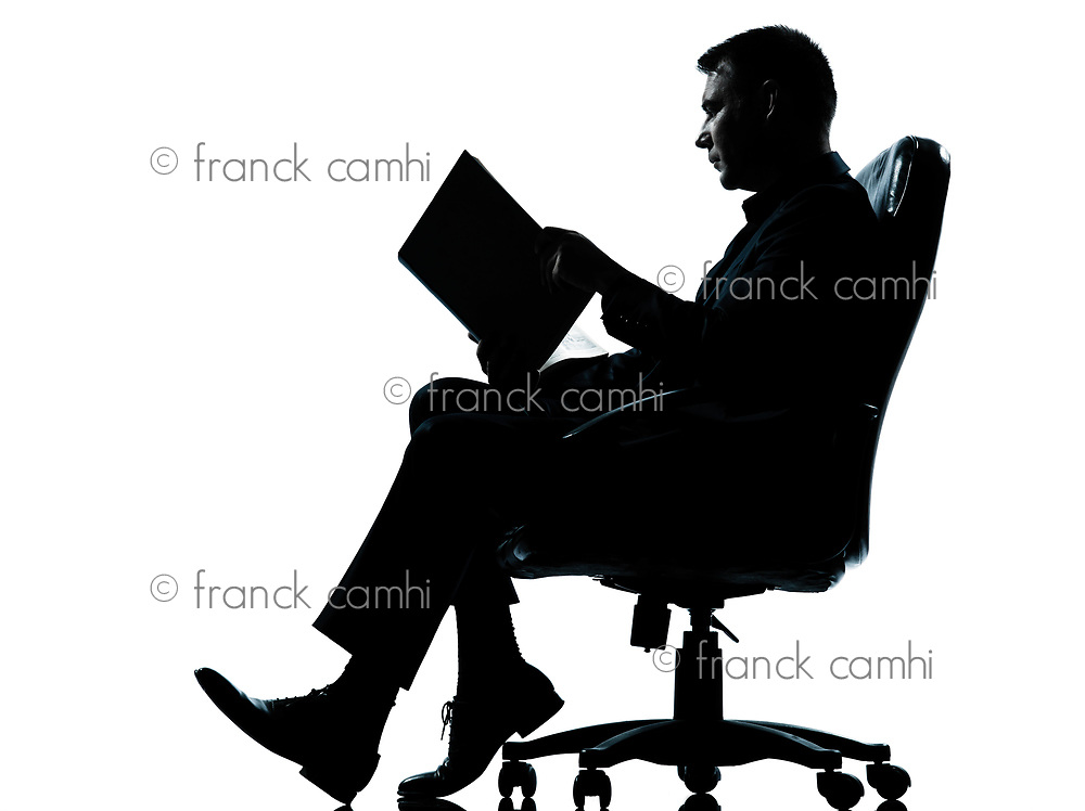 one caucasian business man sitting in armchair reading ancient book silhouette Full length in studio isolated on white background