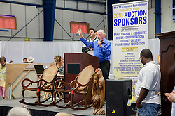Auctioneer George Blackhall opens the bidding for an antique pair of mahogany and cane rockers made by Harrison & Co.  in Barbados circa 1900.  The Hebrew Congregation of St. Thomas presents its seventeenth annual Antiques, Art & Collectibles at Antilles' MCM Center.  The annual silent and live auction supports upkeep and maintenance of the Historic Synangogue and its community programs.   St. Thomas, USVI.  21 February 2016.  © Aisha-Zakiya Boyd