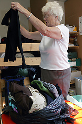 Woman volunteer sorting through clothes at a charity shop,