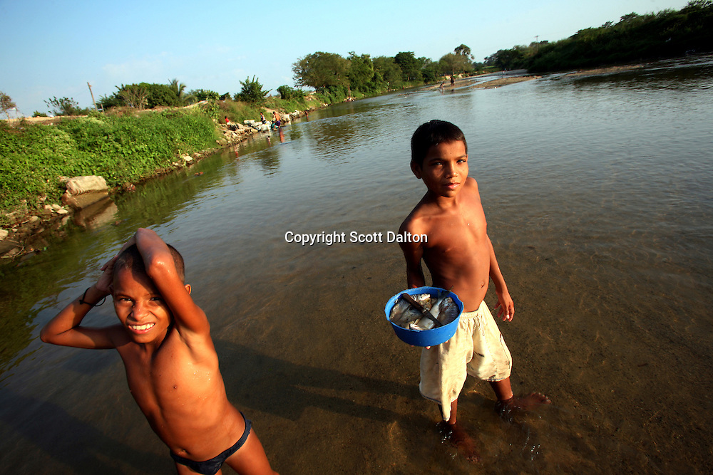 A boy holds a small bucket of fish while in the Aracataca River in Aracataca on Sunday, January 28, 2007.  Aracataca is the hometown of Garcia Marquez, the famed Colombian author most noted for his novel One Hundred Years of Solitude and also the winner of the Nobel Prize for literature. (Photo/Scott Dalton)
