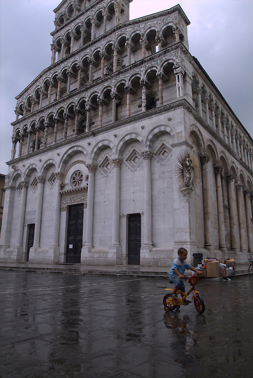 Boy on tricycle in the rain at San Michele in Foro, Lucca, Italy