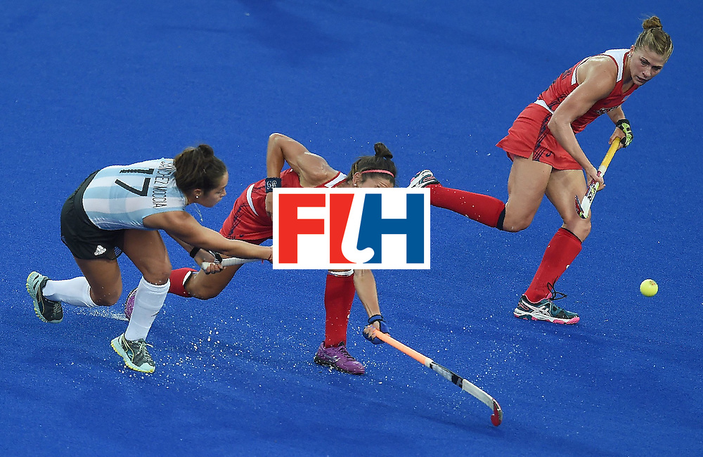 Argentina's Rocio Sanchez (L) hits the ball past the USA Melissa Gonzalez (C) during the women's field hockey Argentina vs USA match of the Rio 2016 Olympics Games at the Olympic Hockey Centre in Rio de Janeiro on August, 6 2016. / AFP / MANAN VATSYAYANA        (Photo credit should read MANAN VATSYAYANA/AFP/Getty Images)