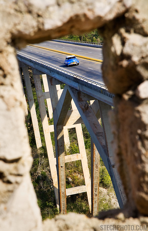 A blue vintage Cuban car crossing a bridge as it enters La Habana province in Cuba.