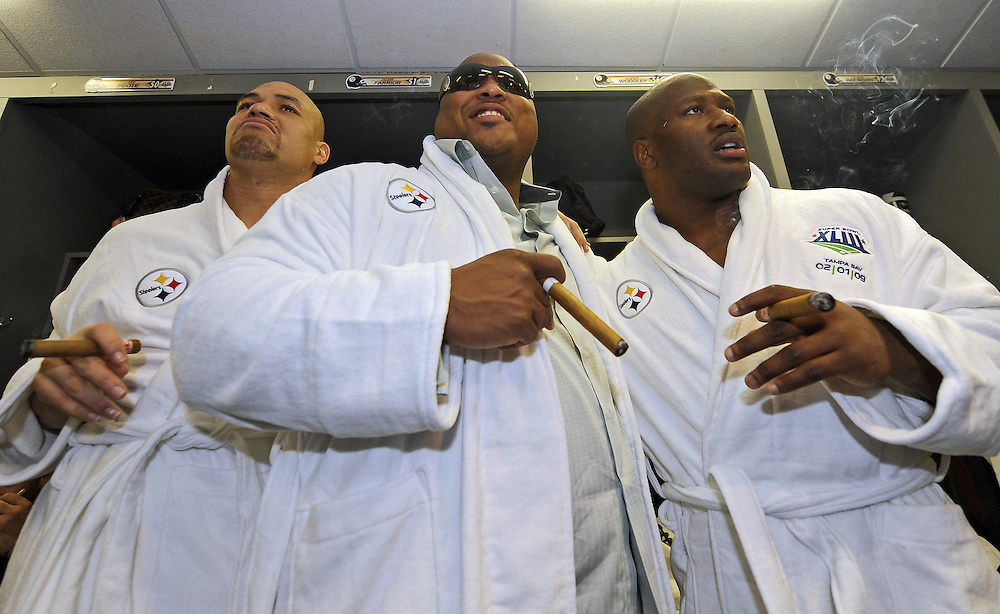 TAMPA, FL - February 1:  James Farrior #51, Casey Hampton #98 and James Harrison #92 of the Pittsburgh Steelers celebrate with cigars in the locker room after defeating the Arizona Cardinals during Super Bowl XLIII on February 1, 2009 at Raymond James Stadium in Tampa, Florida. The Steelers won the game by a score of 27-23.