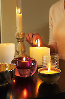 Woman Lighting Candles on table mid section close-up