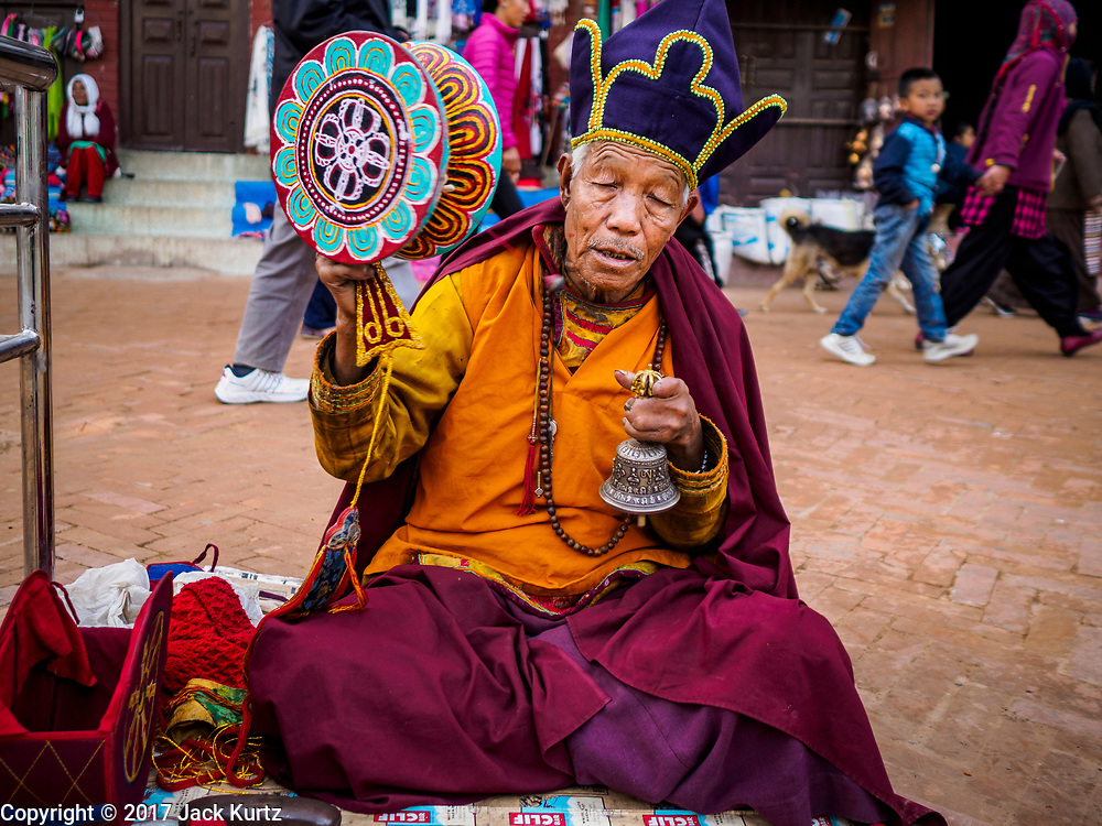 16 MARCH 2017 - KATHMANDU, NEPAL: A Buddhist monk prays during morning payers in front of Boudhanath Stupa in Kathmandu. The stupa is the holiest site in Nepali Buddhism. It is also the center of the Tibetan exile community in Kathmandu. The Stupa was badly damaged in the 2015 earthquake but was one of the first buildings renovated.      PHOTO BY JACK KURTZ