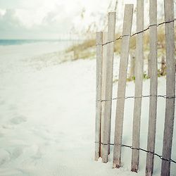 Beach fence in Pensacola Beach Florida retro photo in beige and teal. Pensacola Beach is a coastal city in the Emerald Coast area of the Southeastern United States. Photo is vertical and high resolution. Copyright ⓒ 2018 Paul Velgos with All Rights Reserved.
